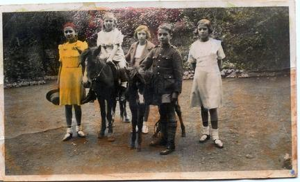 Hand tinted photograph of Five children with two ponies