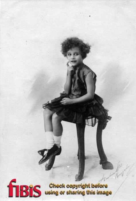 Studio portrait of a young girl sitting on a stool