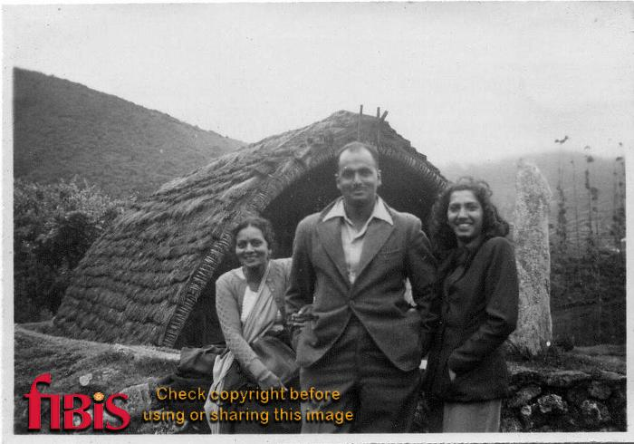 Man and two women outside a hut
