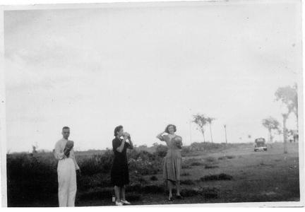 Man and two ladies having a drink from flask