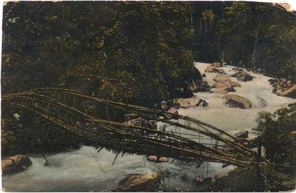 Man on wooden bridge over river
