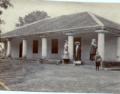 Three women and two children outside a building